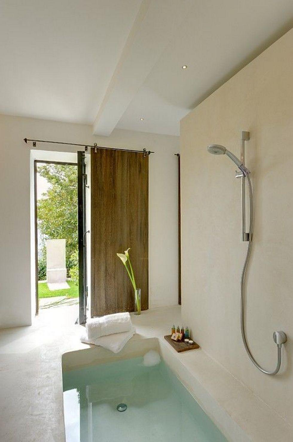 Phòng tắm đơn giản và tự nhiên bằng bê tông và đá, với bồn tắm trũng và cửa trượt để hít thở không khí trong lành