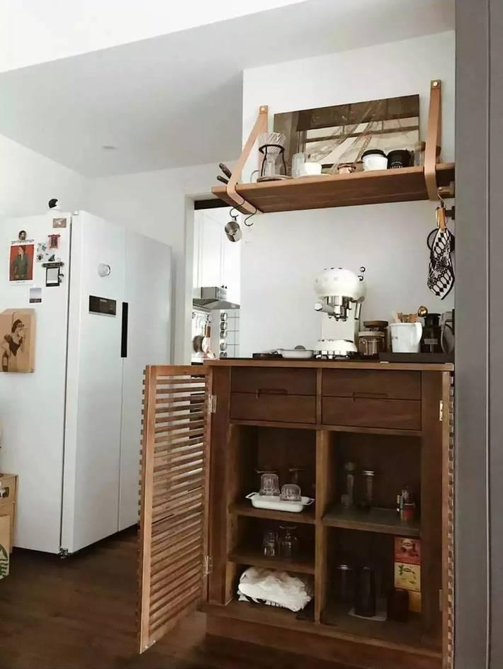 Một chiếc tủ đựng ly, cốc, đồ uống bằng gỗ theo hơi hướng hoài cổ được đặt gần lối vào