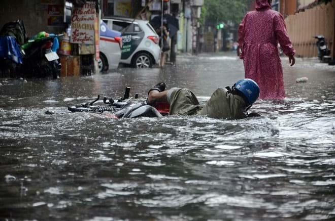Một người đàn ông đi xe máy đã bị ngã do nước ngập sâu, không thể phát hiện chướng ngại vật. Ảnh: Tri Thức Trẻ