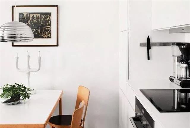 Nhà bếp đầy cá tính với việc bổ sung một vài phụ kiện độc đáo như đèn mặt dây chuyền, nến dân gian và linocut tượng hình trong nhà bếp Scandinavia này.
