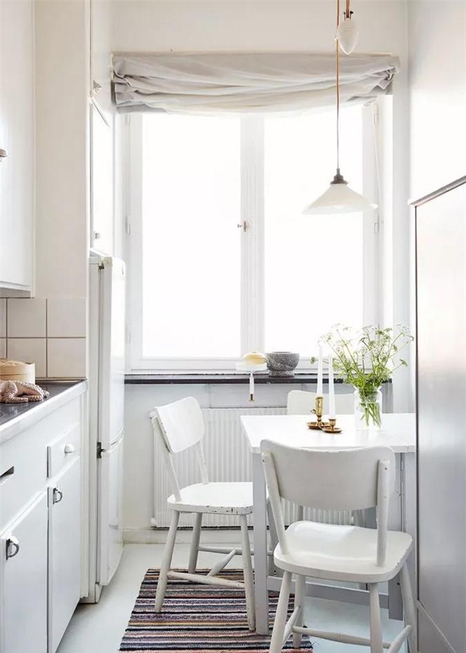 Nhà bếp nhỏ với các tủ màu trắng sáng và đèn mặt dây chuyền không đối xứng, theo đó là sự pha trộn thú vị của đồ nội thất theo phong cách đồng quê retro và rèm cửa vải lanh.
