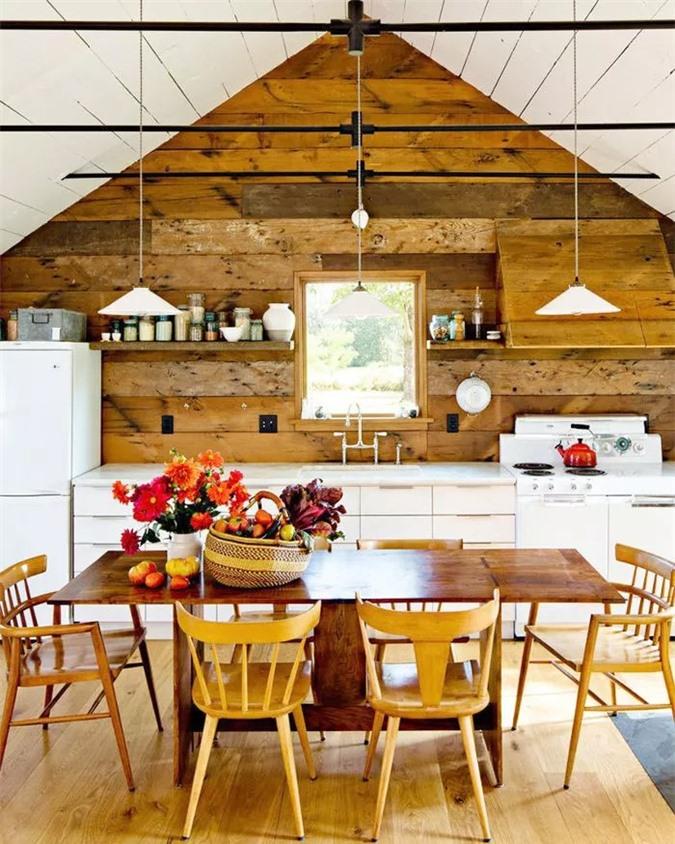 Bức tường ốp gỗ mộc mạc kết hợp liền mạch với các kệ nổi. Đồ nội thất bằng gỗ cũng làm tốt công việc phản ánh kiến trúc nên đứng trong nhà bếp này, bạn có cảm giác hòa quyện vào cả phòng ăn trang trọng.