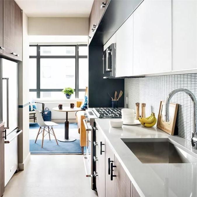 Nhà bếp nhỏ này cho cái nhìn tinh vì với bề mặt sơn mài, tủ gỗ sáng màu và các thiết bị hoàn toàn mới.