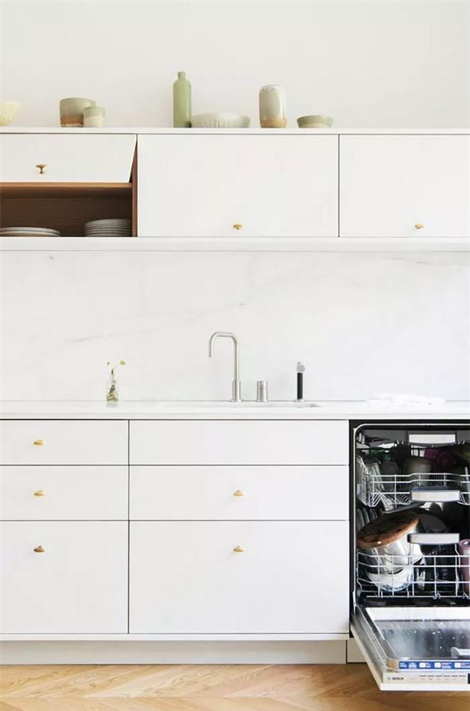 Hầu như không đủ chỗ để quay vòng trong căn bếp nhỏ bé này, nhưng nhà thiết kế đã làm một công việc tuyệt vời để ngăn chặn cảm giác ngột ngạt bằng cách sử dụng tủ hiện đại, sạch sẽ và bảng màu trắng.