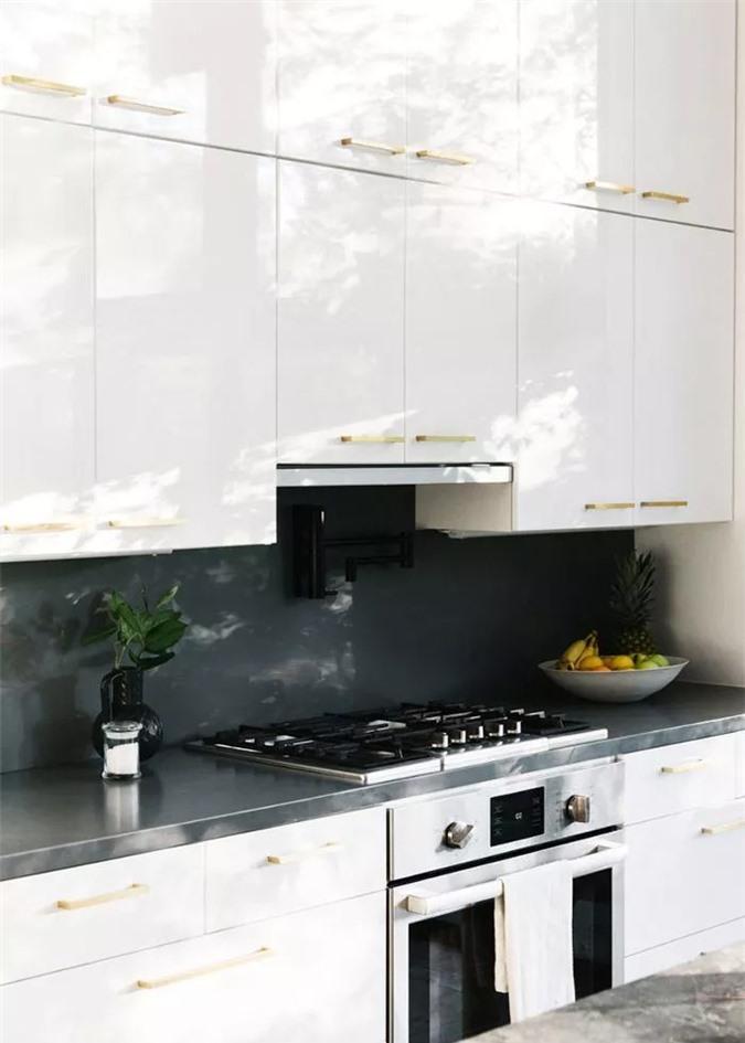 Nhà bếp này có thể nhỏ nhắn, nhưng các vật liệu xa xỉ như mặt bàn bằng đá cẩm thạch đen và lò nướng/bếp cao cấp, mang lại cho nó một hiệu ứng trang sức tốt. Trong những không gian hẹp như thế này, quá nhiều hoa văn hoặc màu sắc có thể bị áp đảo, vì vậy nhà thiết kế đã chọn cho tủ kem và chỉ cần một chút hoa văn trong một tấm thảm xương cá.