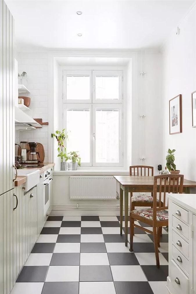 Nhà bếp nhỏ xinh này có rất nhiều thứ để yêu thích: kệ mở đơn giản, máy hút mùi không cầu kỳ, mặt bàn bằng gỗ mộc mạc, tủ gỗ màu xanh nước biển tuyệt đẹp và sàn lát gạch đen trắng cổ điển.