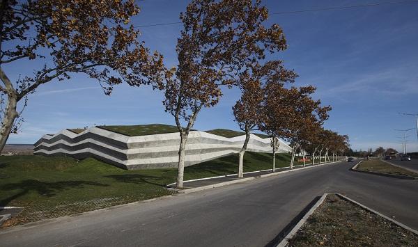 Nhà máy có hình dạng chữ L, có mái thảm thực vật, nằm gọn dọc theo hai cạnh của một khuôn viên chứa nhiều cây xanh, không gian thoáng đãng, tươi mát