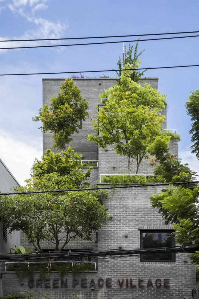 Cận cảnh công trình với những bức tường gạch thô mộc hòa quyện với cây xanh