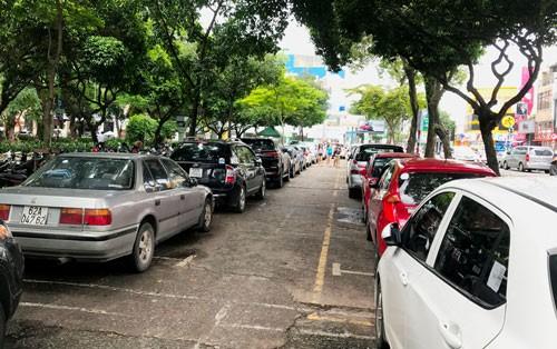 Công viên Lê Văn Tám (quận 1, TP HCM) - nơi vừa hủy dự án xây dựng bãi đậu xe - đang tận dụng một phần làm bãi đậu ôtô do nhu cầu lớn Ảnh: GIA MINH