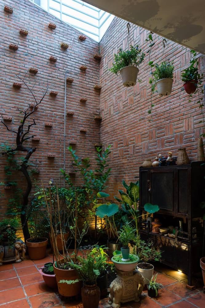 Trên tường gạch thô KTS còn tạo những kệ đặt cây đơn giản nhưng đầy nghệ thuật