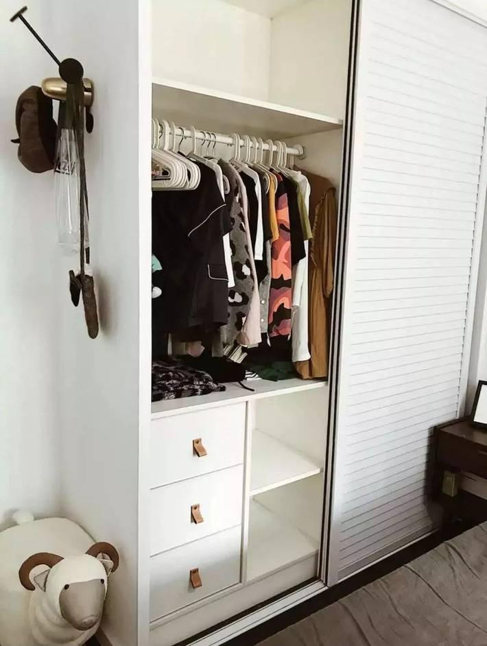 Một chiếc tủ đựng đồ màu trắng ngăn nắp được đặt trong phòng ngủ