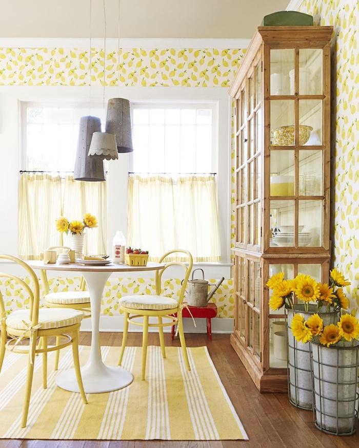 Giấy dán tường in hình quả chanh giúp phòng bếp tươi sáng hơn hẳn. Bạn có thể thêm chút màu vàng chanh cho phòng bếp với rèm cửa và ghế ăn cùng màu.