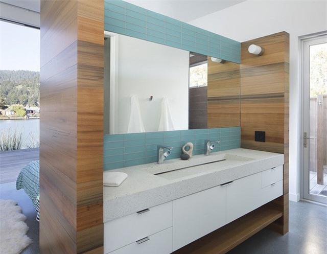 Bạn cũng có thể sử dụng gam màu xanh để tạo điểm nhấn cho gương treo tường ở khu vực bồn rửa tay như cách này