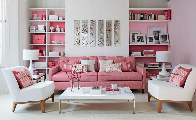 Nếu phòng khách chỉ độc một màu trắng nó sẽ trở nên nhàm chán. Vậy nên kệ sách và ghế sofa màu hồng khiến căn phòng trở nên trẻ trung và sinh động hơn.
