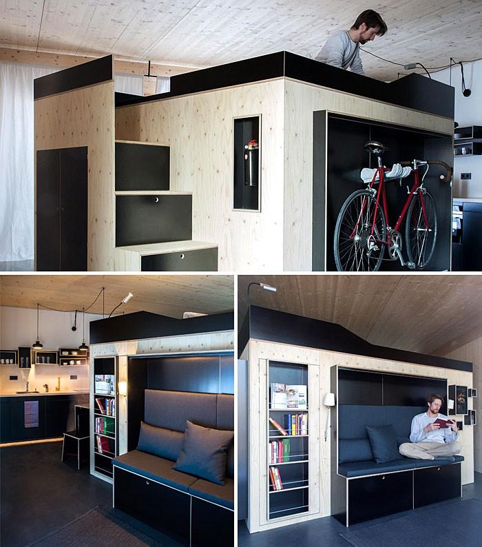 Nhà thiết kế Nils Holger Moormann đã tìm kiếm để tối ưu hóa việc sắp xếp cuộc sống trong các căn hộ siêu nhỏ hiện đại. Đồ nội thất tập trung tại một góc giữa nhà với sắc màu tối bao trùm, chất liệu hiện đại, thoải mái thiết kế thêm không gian giường đôi phía trên, cầu thang có chức năng lưu trữ, tủ quần áo không cửa và nhiều tính năng linh hoạt khác đáp ứng việc tìm kiếm lối sống hiện đại để tối ưu hóa từng cm trong không gian căn hộ nhỏ.