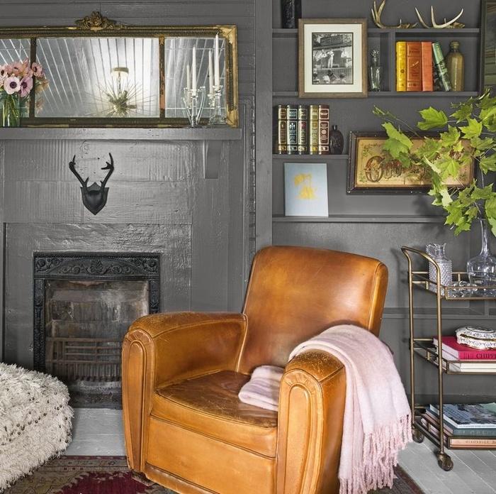 Để giúp nhà ấm cúng ngay lập tức, bạn hãy sơn tất cả các bức tường, đồ dùng, và thậm chí trần nhà bằng một màu đậm, tối. Để chiếc ghế da tạo điểm nhấn cho phòng khách.