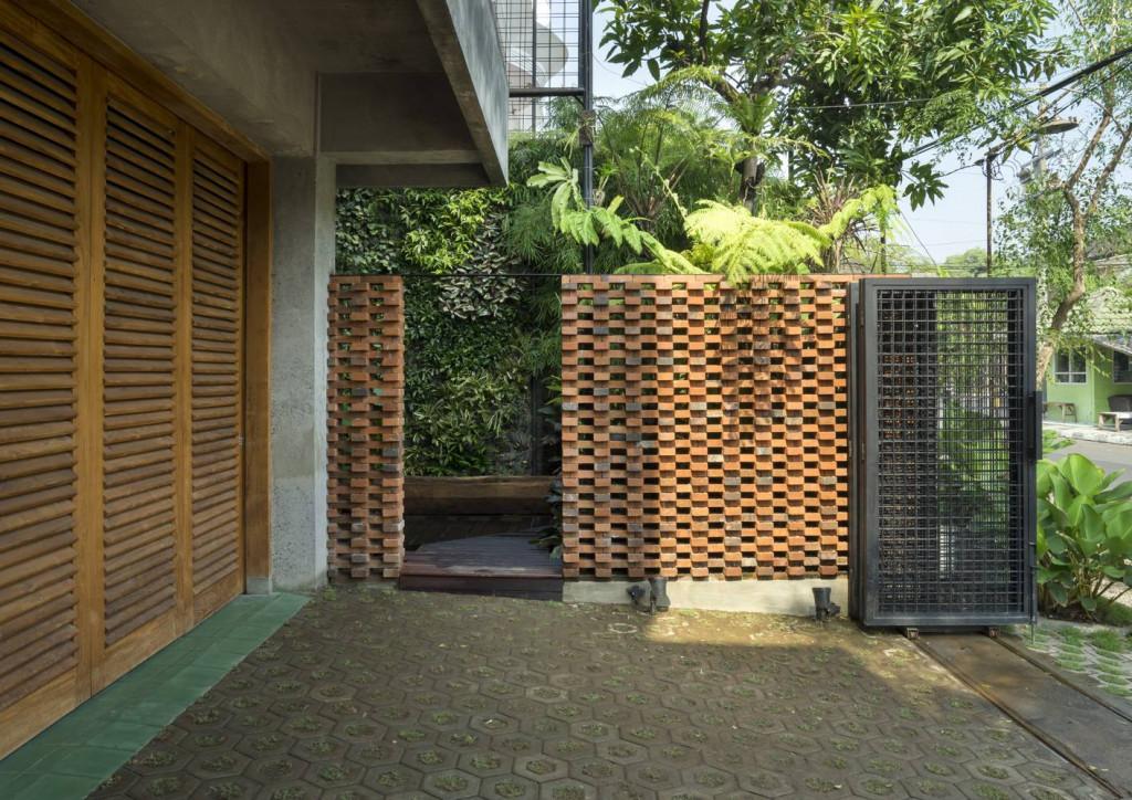 Cổng của căn nhà gạch rất mộc mạc nhưng không kém phần tinh tế với bức tường gạch xếp chồng