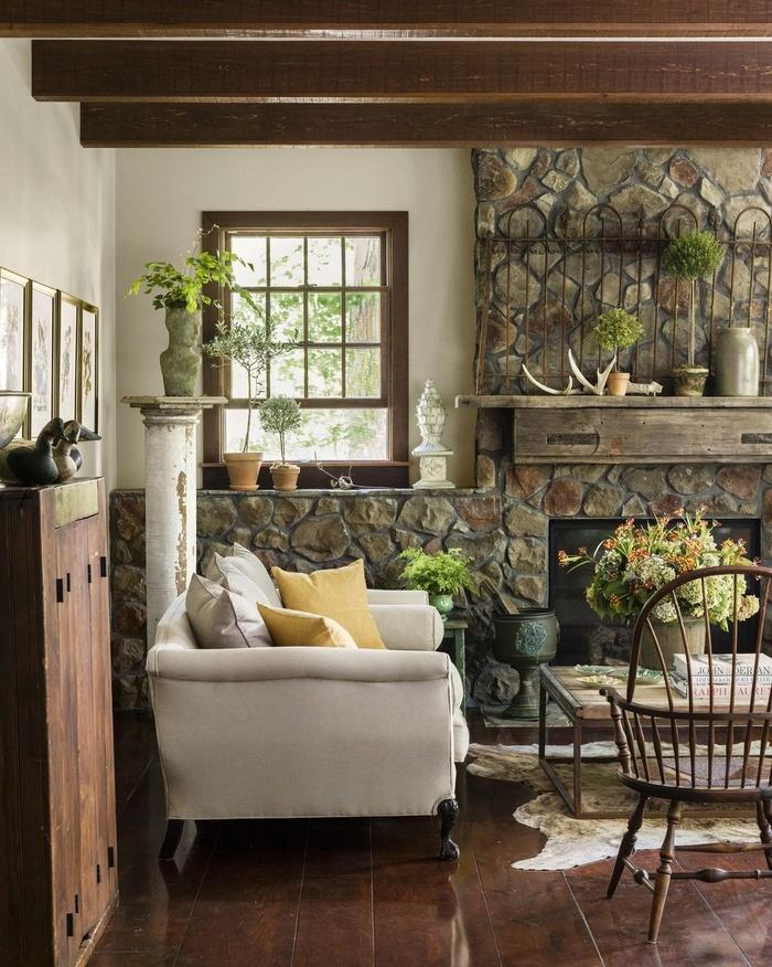 Đá tự nhiên cùng các đồ nội thất mộc mạc như một cổng sắt cổ và đồ sành sứ giúp phòng khách ấm cúng hơn hẳn.