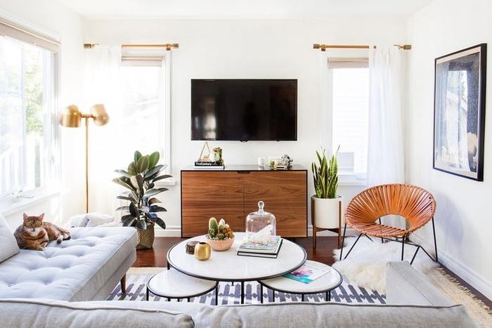 """Ghế sofa hình chữ """"L"""" tối giản là một cách tuyệt vời để tối đa hóa chỗ ngồi trong phòng khách nhỏ. Bộ bàn cà phê cùng chiếc ghế dệt bằng da vừa nhỏ gọn, sành điệu vừa không tốn nhiều diện tích. Các chậu cây mang lại sự cân bằng và vẻ đẹp cho căn phòng."""