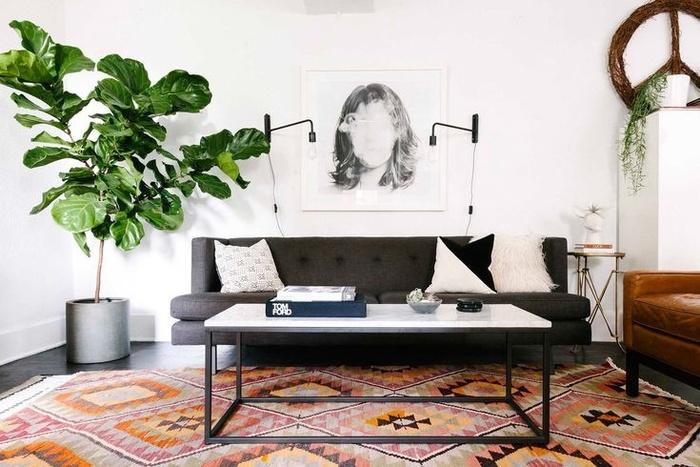 Đồ nội thất tối màu tạo thêm chiều sâu cho phòng khách nhỏ màu trắng. Ghế sofa màu xám và ghế phụ không làm không gian phòng nhỏ đi. Nếu có trần nhà cao, bạn có thể để cây trong nhà nhằm tạo sự tương phản với bức tường trắng. Tấm thảm dưới sàn có tông màu cam giúp căn phòng hài hòa hơn.