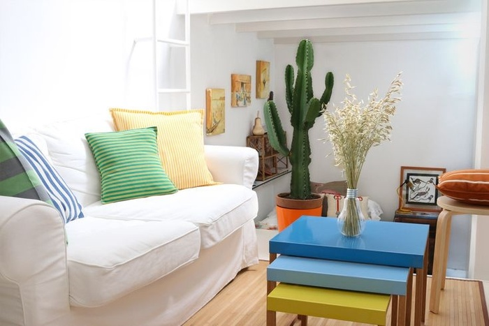 Khi có phòng khách nhỏ, bạn hãy tìm những đồ nội thất có kích thước nhỏ ấm cúng như ghế sofa sang trọng trong không gian này. Chiếc bàn đầy màu sắc cùng các đồ nội thất màu nâu giúp phòng khách ấm cúng hơn.