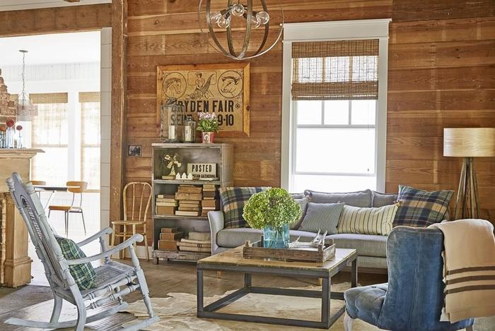 Để phòng khách mộc mạc hơn bạn hãy tạo bức tường gỗ. Tông màu ấm của bức tường gỗ cũng tạo ra phông nền ấm cúng cho đồ nội thất và gối nhiều màu xám và xanh lam khác nhau.