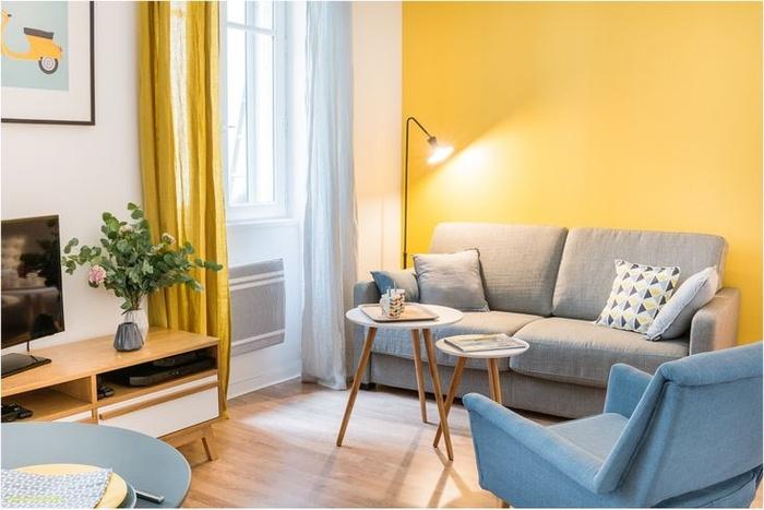 Một bức tường màu vàng sáng làm nổi bật phòng khách nhỏ. Hai món đồ nội thất nhỏ có màu sắc nhẹ nhàng, ghế sofa và ghế bành mang lại sự thoải mái cho chủ nhà. Những chiếc bàn cà phê nhỏ xíu tiết kiệm diện tích ngôi nhà.