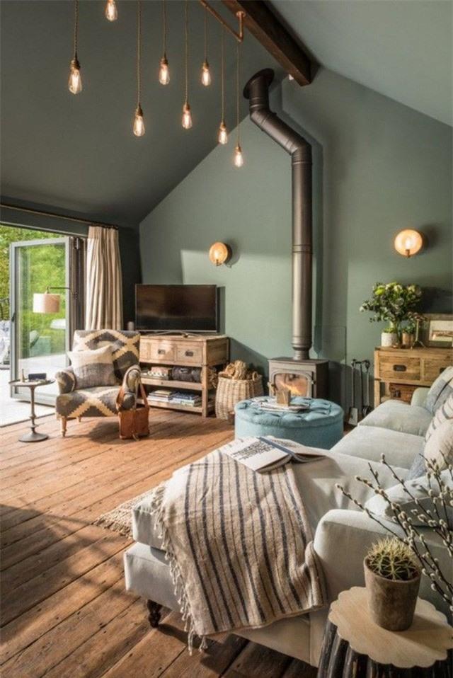 Đèn tường và bóng đèn trần rủ xuống từ một trần gỗ xinh xắn tạo sự hiện đại cho phòng khách