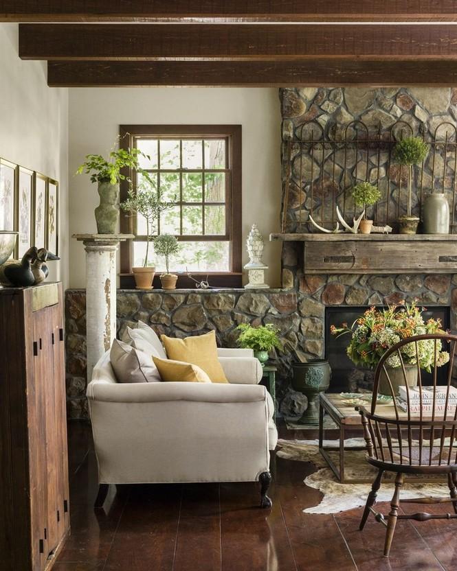 Đá tự nhiên cùng các đồ nội thất mộc mạc như một cổng sắt cổ và đồ sành sứ giúp phòng khách ấm cúng hơn hẳn