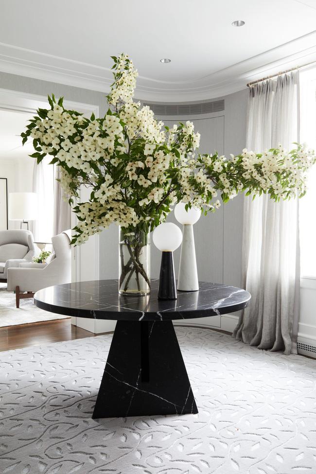 Ngay cả một không gian siêu trang trọng và hiện đại cũng có thể cảm thấy mời gọi với lọ hoa phù hợp ở trung tâm. Các họa tiết hoa trong thảm làm dịu đi màu xám mát mẻ.