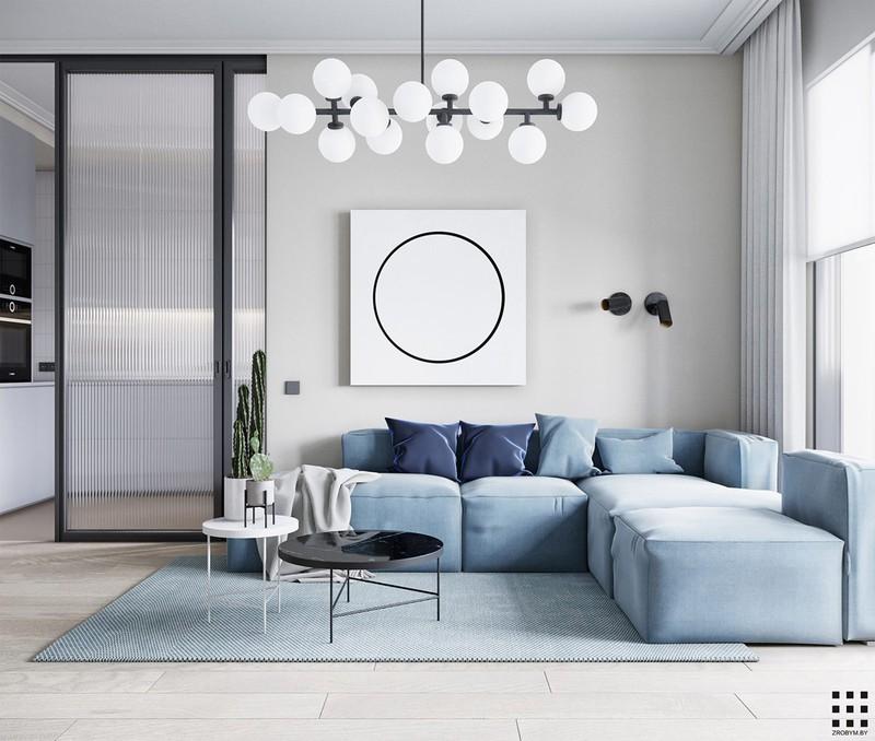 Bước vào phòng khách bạn sẽ ngạc nhiên trước vẻ đẹp nhẹ nhàng của ghế sofa màu xanh pastel. Ghế ôm trọn một tấm thảm màu xanh, bàn nước cùng đèn chùm độc đáo bên trên.