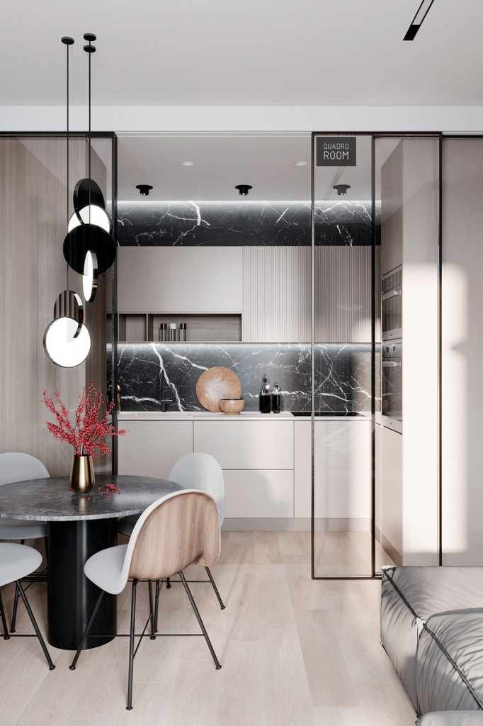 Một nhà bếp nhỏ được ngăn cách với phòng ăn và phòng khách bằng một bộ cửa kính trượt. Độ trong suốt của kính giúp không gian khiêm tốn dường như rộng hơn