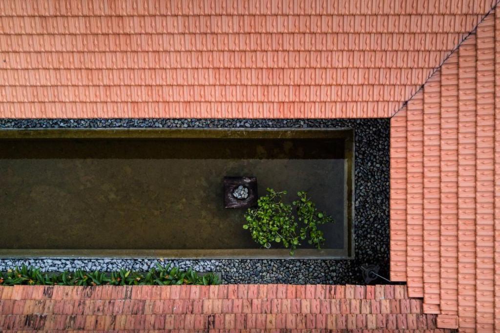 """Chủ nhà ủng hộ khi các kiến trúc sư đề xuất không gian """"đóng ngoài mở trong"""". Phần nhà ba gian cũ nối liền với phần nhà ở mới bằng hành lang mở, ở giữa có khoảng đệm là hồ nước."""