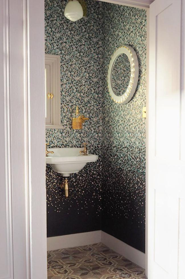Một hình nền lấy cảm hứng từ sơn splatter vừa bổ sung và tương phản với gạch theo phong cách Địa Trung Hải cổ điển. Cùng với chiếc gương, hình nền mang đến cho phòng tắm nhỏ bé này một nét rất hiện đại