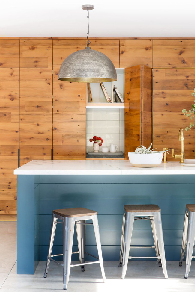 Trong nhà bếp này của Regan Baker Design, mặt tiền gỗ từ sàn đến trần che giấu các tủ và mặt bàn