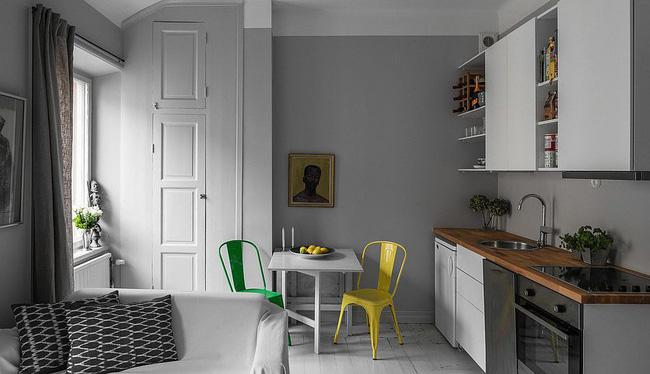 Nhà bếp đơn sắc với ghế đầy màu sắc cho khu vực ăn sáng