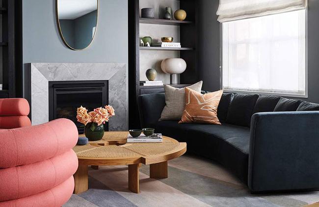 Để có một điểm nhấn trong phòng khách, bạn hãy nghĩ đến bàn uống nước ấn tượng và chọn các sắc thái bổ sung. Ví dụ, những bông hồng đào bật bên trong căn phòng màu xanh xám này hài hòa với ghế bành san hô.