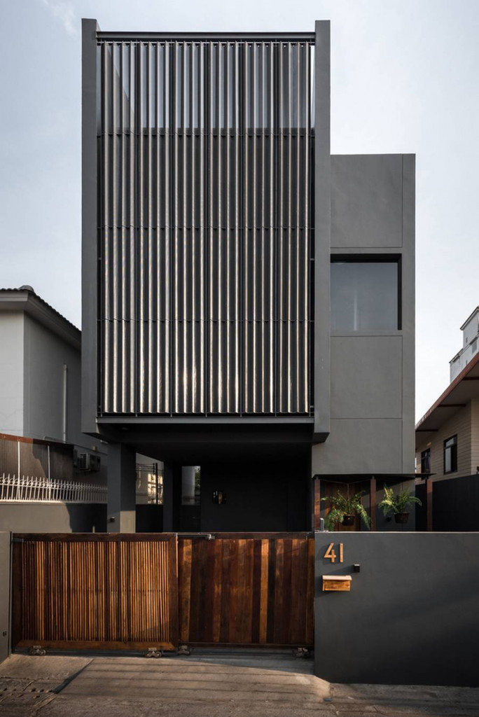 Thiết kế mặt tiền của căn nhà ba tầng với chiếc cổng gỗ nổi bật trong một tổng thể màu ghi xám