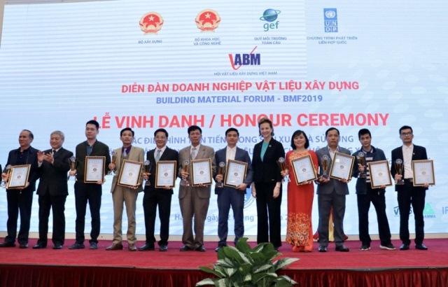 Thứ trưởng Bùi Phạm Khánh và bà Caitlin Wiesen trao giấy chứng nhận và cup tại lễ tôn vinh cho các điển hình tiên tiến trong sản xuất và sử dụng vật liệu xây không nung