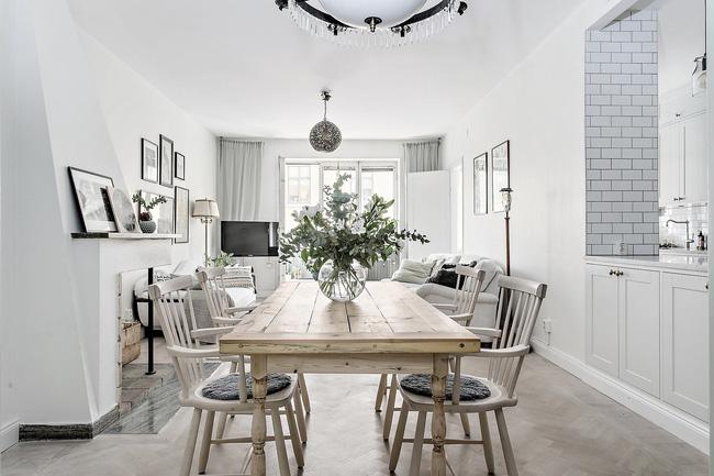 Nối tiếp khu vực phòng khách là một bàn ăn xinh xắn với lọ hoa cũng mang sắc bàng bạc đặc trưng.