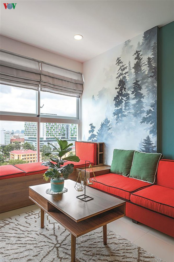 Hình ảnh rừng thông được tái hiện trong phòng khách. Để cân bằng màu sắc bộ sofa có màu đỏ nổi bật trên nền xanh.