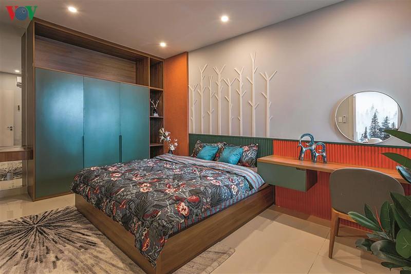 Phòng ngủ chính rộng rãi, với màu xanh và màu cam chủ đạo.