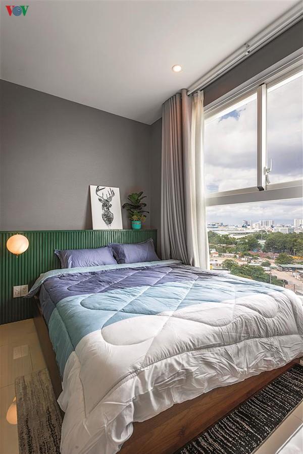 Phòng ngủ nhỏ chan hòa ánh sáng thiên nhiên với mảng đầu giường màu xanh lá.