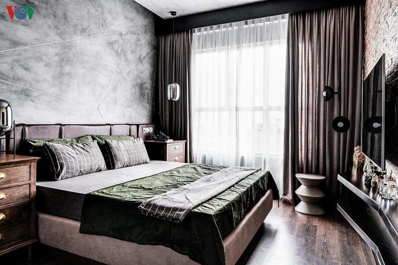 Không gian phòng ngủ chính với tường xi măng mài, sàn gỗ màu sẫm
