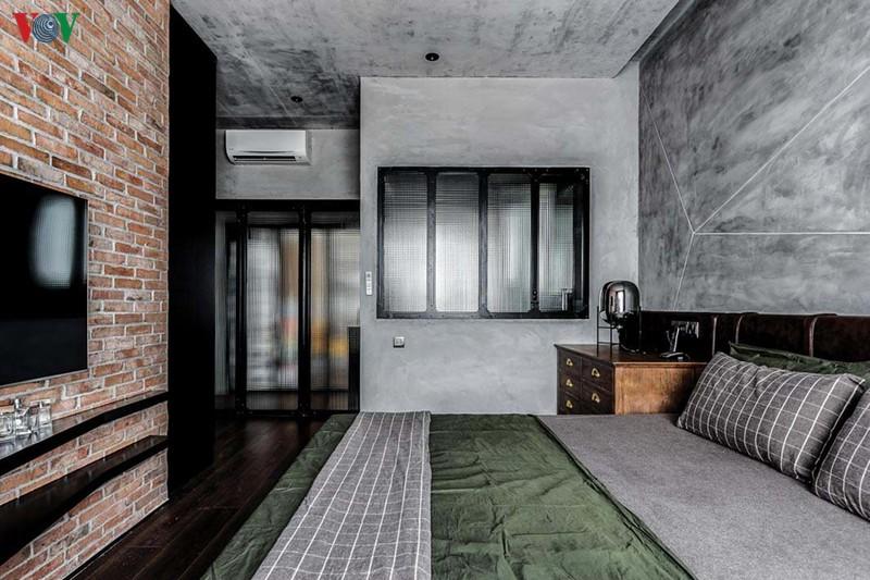 Phía cuối giường là mảng tường gạch trần. Phòng vệ sinh được lấy sáng qua hệ cửa kính mờ