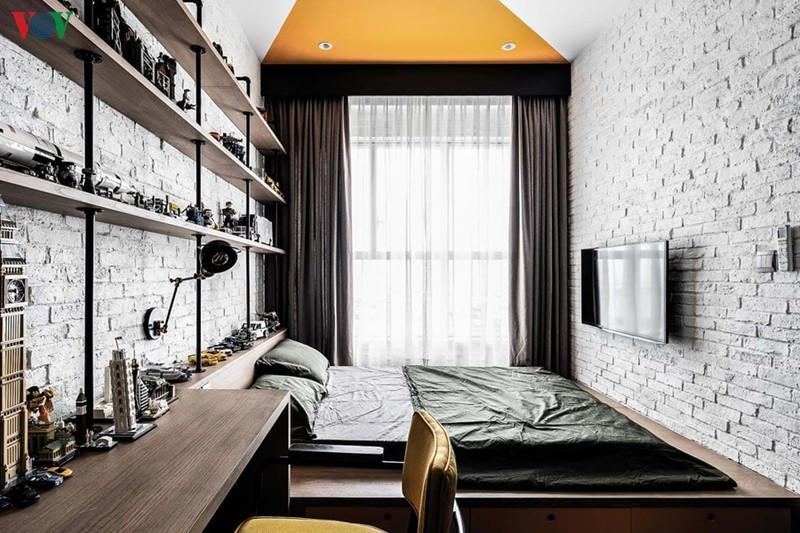 Phòng ngủ con sử dụng tường không trát nhưng sơn trắng để tăng độ sáng. Một mảng trần sơn màu cam làm điểm nhấn