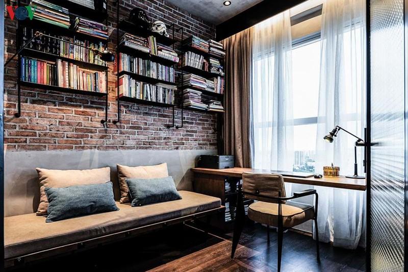 Phòng làm việc có bàn kê sát, hướng ra cửa sổ để tận dụng ánh sáng và tiết kiệm diện tích. Giá sách là những kệ sắt treo trên tường
