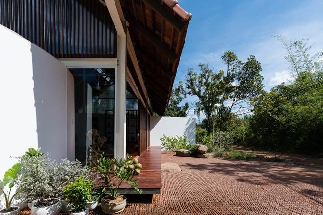 Mặt ngoài nhà có sử dụng kính và các lam gỗ làm vách ngăn giữa bên trong với hiên nhà