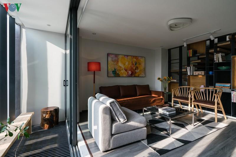 Phía trước phòng khách có một khoảng hiên. Sàn nhà và đồ nội thất có màu xám chủ đạo điểm xuyết với một số màu khác.