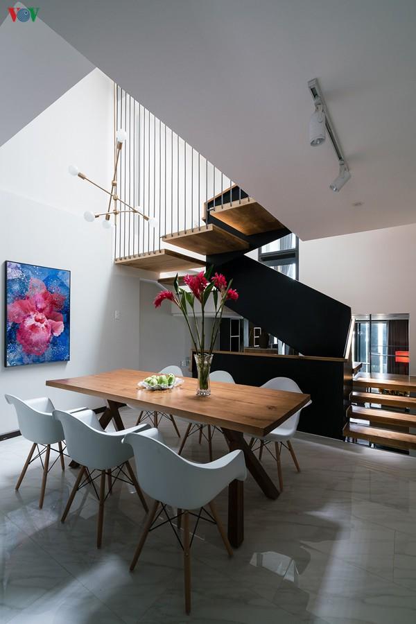 Cầu thang được thiết kế như một khối điêu khắc là điểm nhấn trong không gian. Lan can cầu thang là những mảng thép sơn màu xám sẫm.
